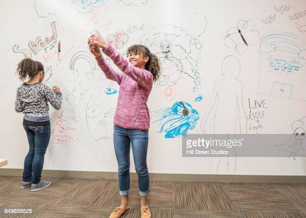 Girl taking selfie near whiteboard