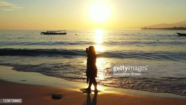 girl taking selfie photos with smartphone on empty beach at sunset golden hour with orange sky reflecting on sea surface - golden hour stock pictures, royalty-free photos & images