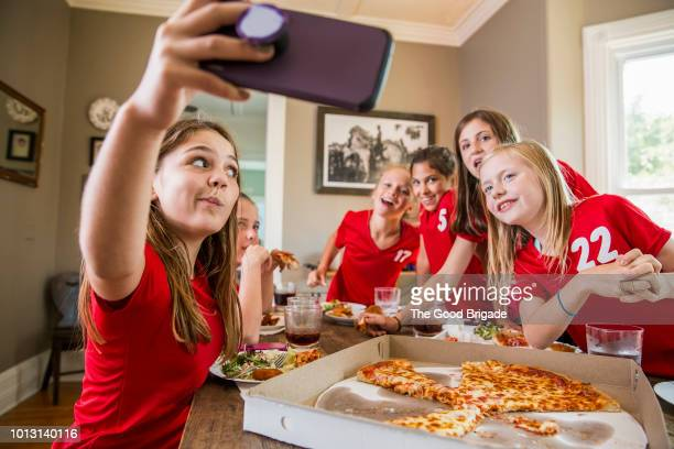 girl taking selfie with friends while eating pizza - sports uniform stock pictures, royalty-free photos & images