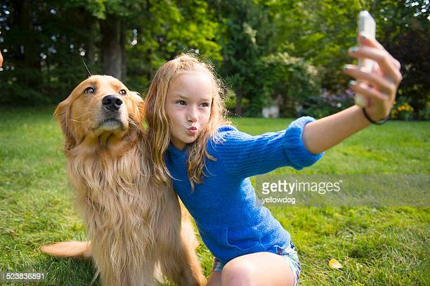 Girl taking selfie with pet dog in garden