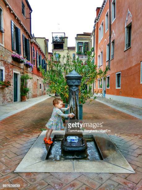 Girl Taking Water From Drinking Fountain Amidst Buildings In City