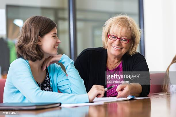 Girl taking with tutor while studying for exam after school