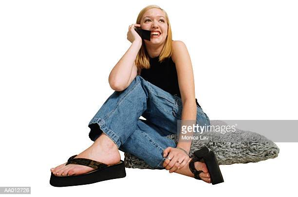 girl talking on a cellular phone - girl wear jeans and flip flops stock photos and pictures