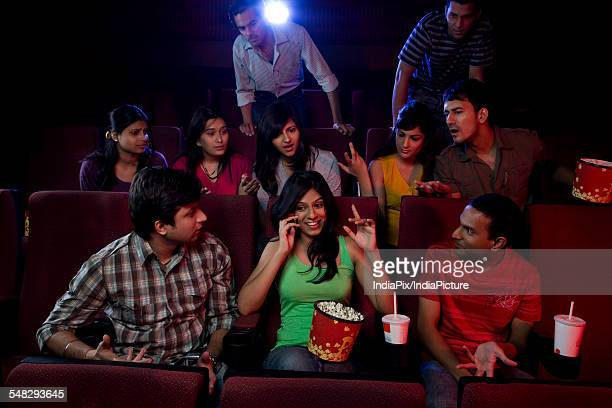 girl talking on a mobile phone in a cinema hall - inconvenience stock pictures, royalty-free photos & images
