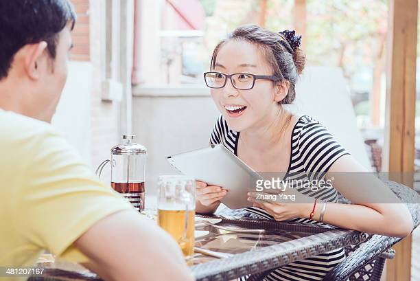 Girl talking to her friend in cafe with an iPad in her hands