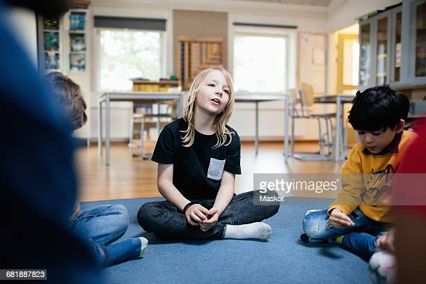 girl talking while sitting with friends on floor in classroom - montessori education stock pictures, royalty-free photos & images