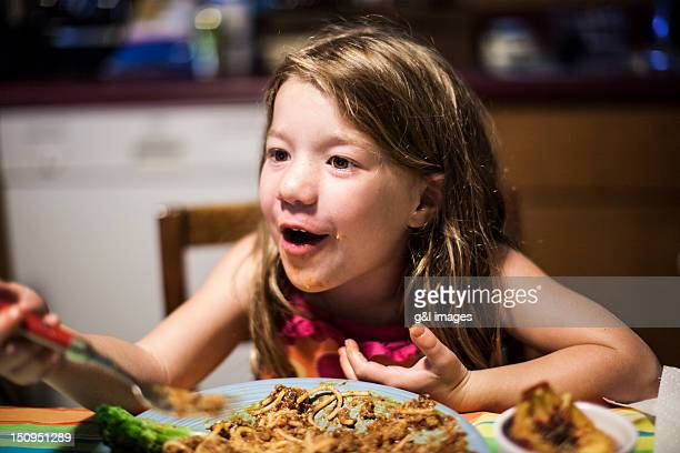 girl (5 yrs) talking with family at dinner table