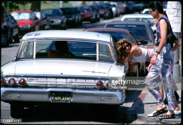 Girl talks to a man driving a classic car on Melrose Avenue August 8, 1993 West Hollywood , Los Angeles, California