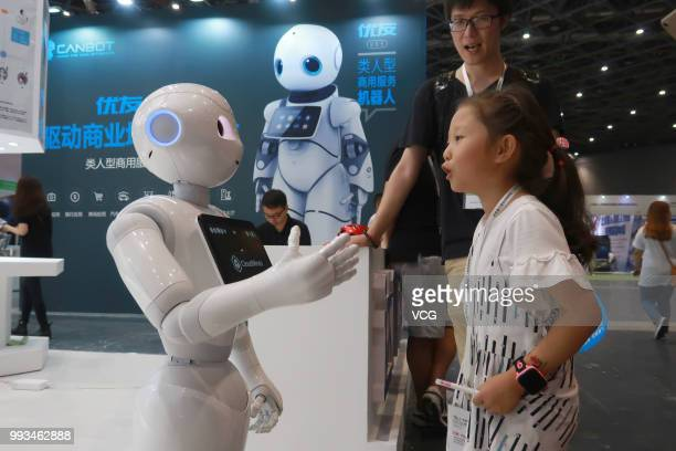 A girl talks with an AI robot by Canbot during the China International Robot Show 2018 at National Exhibition and Convention Centre in Shanghai China...