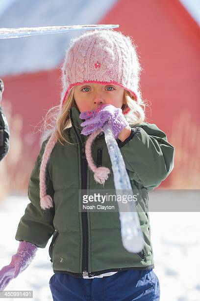 Girl tastes ice cycle in winter