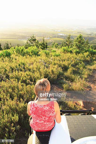 Girl tasting wine as sun sets in the Cape Winelands above Stellenbosch, Western Cape Province, South Africa