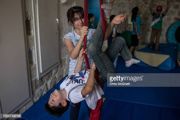 A girl teaches a boy scarf acrobatics at a workshop at the Istasyon Sirkhane Center on July 24 2018 in Mardin Turkey The circus school or Her Yerde...