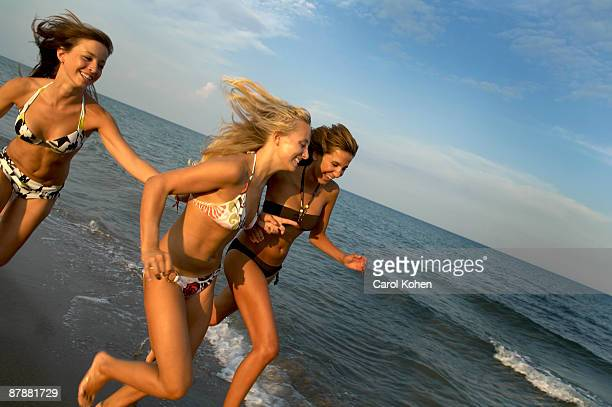 Girl teenagers running on the beach