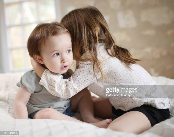 A girl telling a secret to her sister