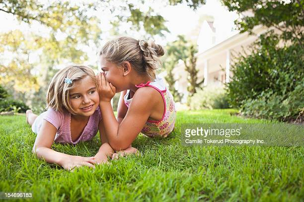 Girl telling younger sister a secret