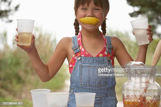 Girl (5-7) tending lemonade stall, lemon wedge in mouth, portrait