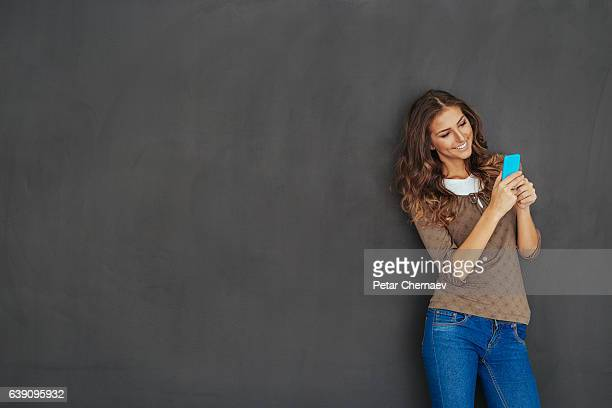 Girl texting in front of a blackboard