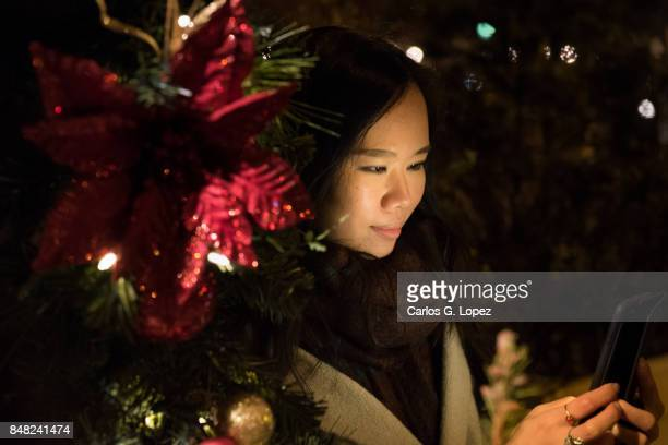 Girl texting on phone surrounded by Christmas decorations - Christmas Shopping