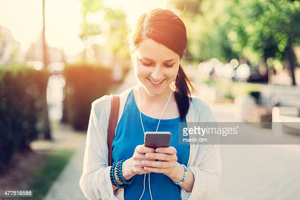 Girl texting on smarthone in the city