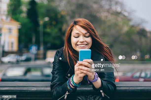 Girl texting on smartphone at the street