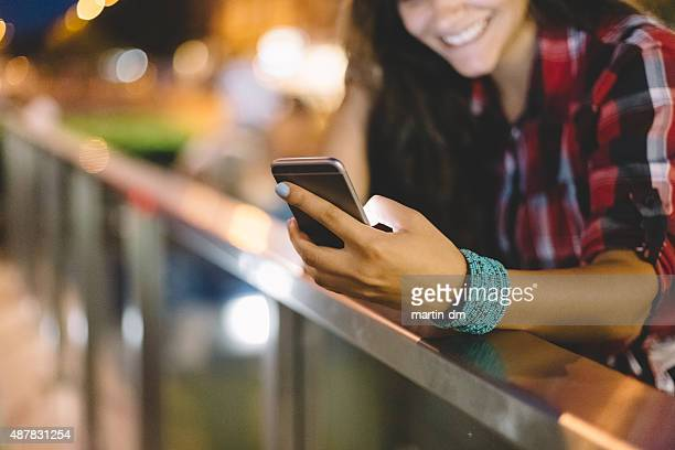 Girl texting on smartphone in the city