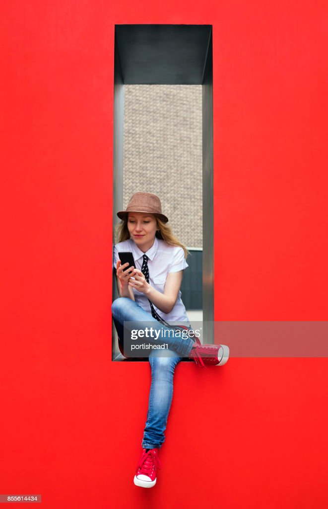 Girl texting on smartphone outside : Stock Photo