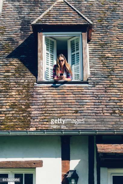 Mädchen-SMS auf dem Dach-Fenster