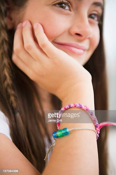 Girl thinking, close up of friendship bracelets