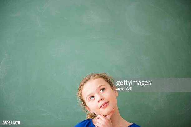 Girl (10-11) thinking in front of green blackboard