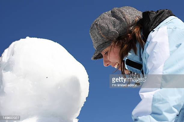 Girl thrilled in making snowman