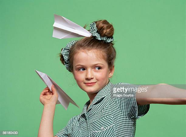 Girl throwing a paper aeroplane