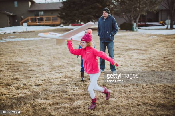 Girl Throwing a toy airplane