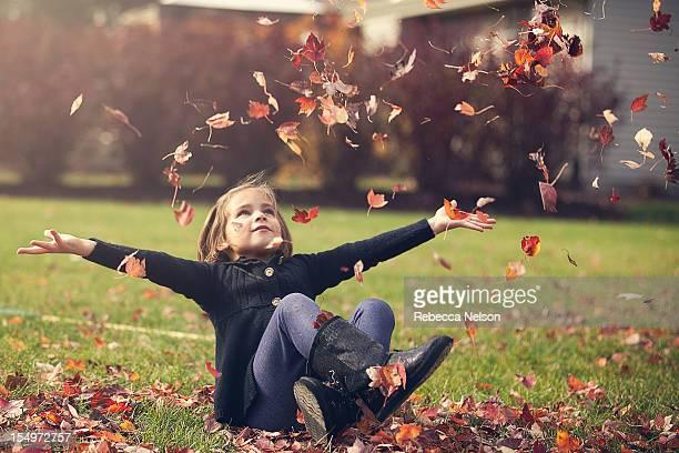 Girl throwing atumn leaves