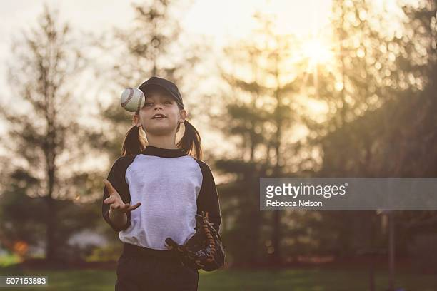 girl throwing baseball up into the air - rebecca nelson stock pictures, royalty-free photos & images