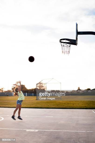 girl throwing basketball to make a goal on court against sky - shooting baskets stock pictures, royalty-free photos & images
