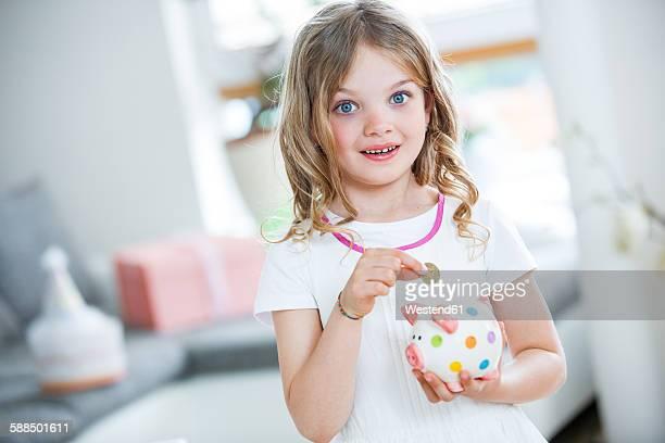 Girl throwing coin into piggy bank