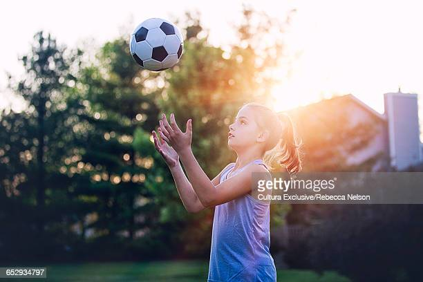 Girl throwing football in the air