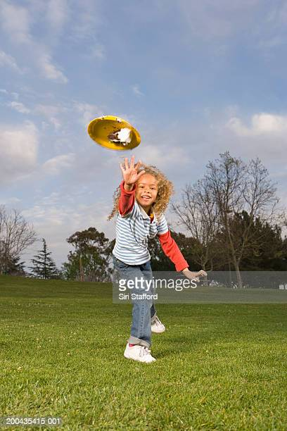Girl (4-6) throwing paper plate with cake