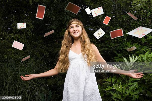 Girl (10-11) throwing playing cards in air, in garden, low angle view