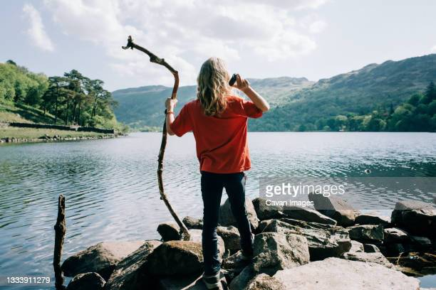 girl throwing stones and sticks into the water in wales, uk - small stock pictures, royalty-free photos & images