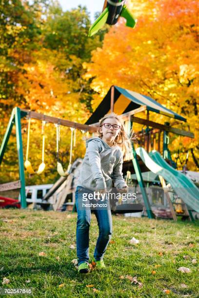 girl throwing toy rocket mid air in garden - heshphoto stock pictures, royalty-free photos & images