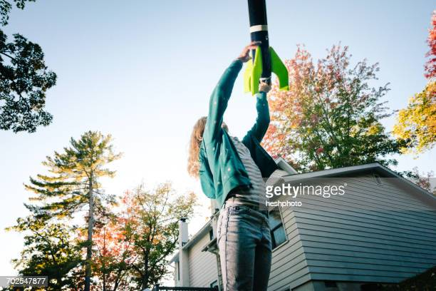 girl throwing toy rocket upward toward blue sky - heshphoto stock pictures, royalty-free photos & images