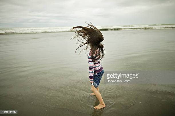 Girl throws back her long hair at the beach