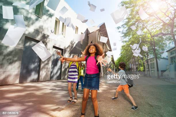 Girl throws papers happy and standing near school