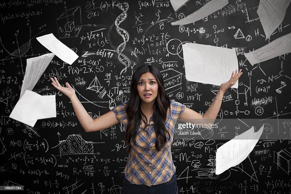 Girl throws up paper near math chalkboard : Stock Photo