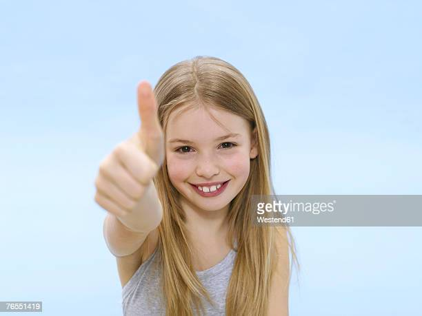Girl (10-11) stand with thumbs up, smiling, close-up, portrait