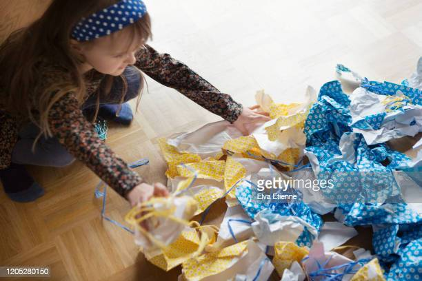 girl (6-7) tidying up discarded wrapping paper after a birthday celebration - messy house after party stock pictures, royalty-free photos & images