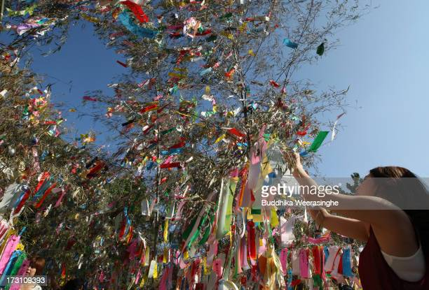A girl ties a paper strip with her wish on it onto a bamboo decoration during the Tanabata festival at the Hatamono shrine on July 7 2013 in Osaka...