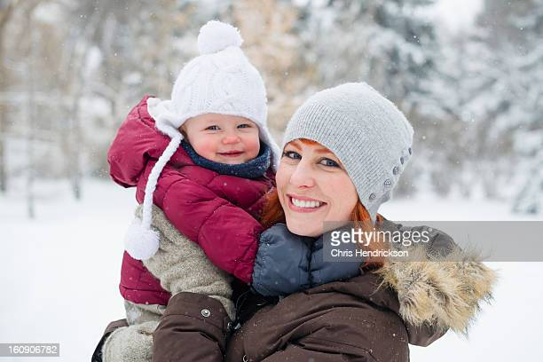 Girl toddler and mother in winter snow