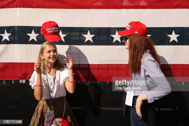 Girl tosses her Make America Great Again hat onto her head while waiting for the start of a campaign rally with U.S. President Donald Trump at...